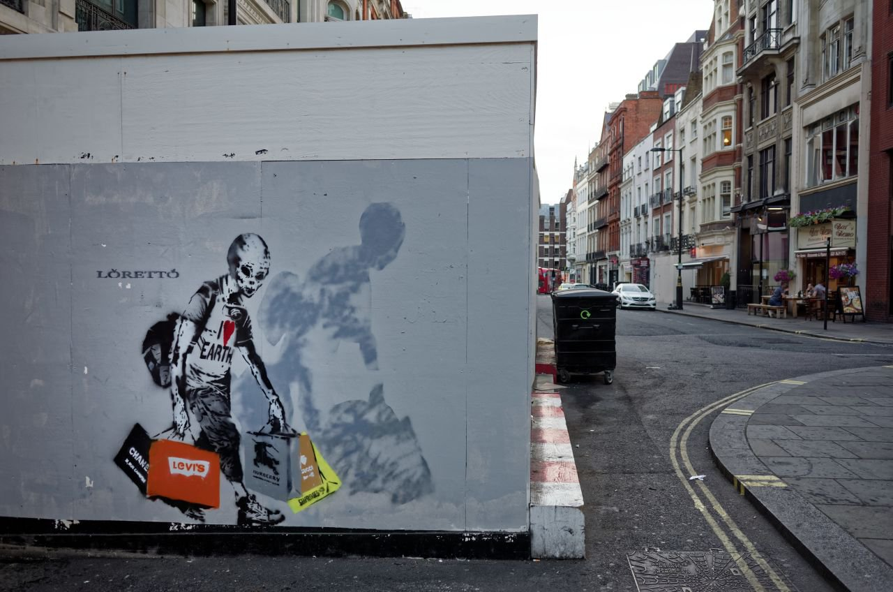 Street art depicting a skeleton wearing an I love earth t-shirt while carrying multiple branded shopping bags